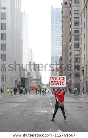 "TORONTO-JUNE 26:  A protester holding a sign which says that this sate has become a ""police state"" right in front of a line of riot police during the G20 Protest on June 26 2010 in Toronto, Canada."