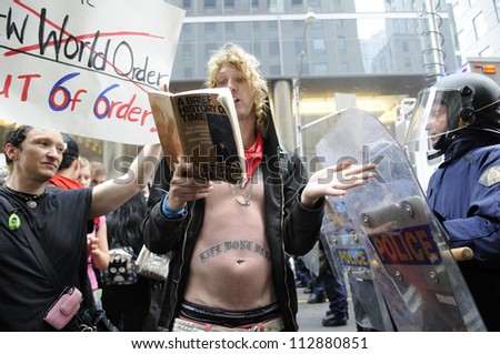 "TORONTO-JUNE 26:   A protester reads out lines from a Stephen Hawking book titled "" A brief history of time "" to the riot police officers  during the G20 Protest on June 26, 2010 in Toronto, Canada. - stock photo"