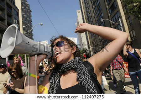 TORONTO-JUNE 25: An angry woman  protester chanting slogans with a microphone during the G20 Protest on June 25, 2010 in Toronto, Canada. - stock photo