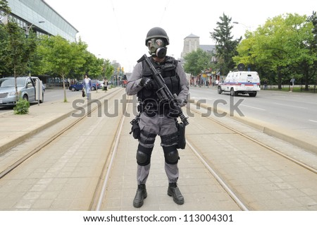 TORONTO-JUNE 27:  An elite police officer patrolling the street car tracks wearing gas masks during the G20 Protest on June 27, 2010 in Toronto, Canada. - stock photo