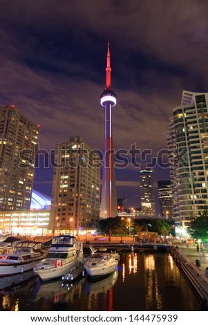 TORONTO - JUNE 29: CN Tower in Toronto at dusk,  lit in red and white in honour of Canada Day, seen from Harbourfront on June 29, 2013. - stock photo