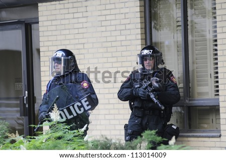 TORONTO-JUNE 25:  Elite snippers taking cover in front of a residential building during the G20 Protest on June 25, 2010 in Toronto, Canada. - stock photo