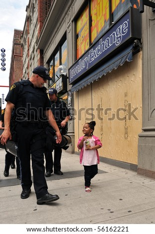 TORONTO-JUNE 27: Friendly interaction between policemen and little girl on Toronto street during G20 protest June 27, 2010 in Toronto. - stock photo