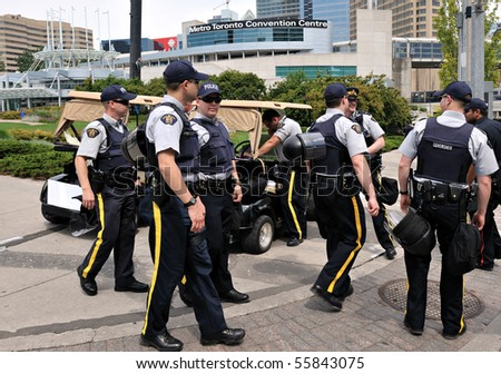 TORONTO-JUNE 23: Heavy police force walk around Metro Toronto Convention Centre in preparation for the G20 Summit on June 23, 2010 Toronto. - stock photo