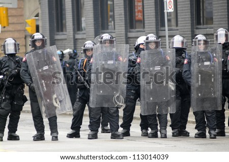 TORONTO-JUNE 26: Male and female riot police officers taking guard during the G20 Protest on June 26, 2010 in Toronto, Canada. - stock photo