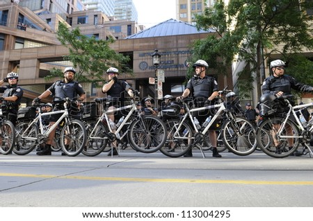 TORONTO-JUNE 28:   Police officers forming a cycle barricade in front of the police headquarters during the G20 Protest on June 28, 2010 in Toronto, Canada. - stock photo