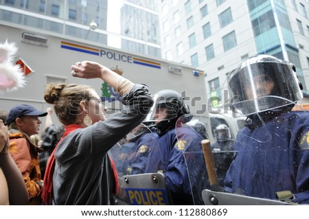 TORONTO-JUNE 26:   Protesters  shouting and yelling in front of the riot  police during the G20 Protest on June 26, 2010 in Toronto, Canada. - stock photo
