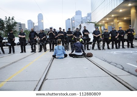 TORONTO-JUNE 26:  Protesters sitting on the streets while the police officers keep a close eye on them during the G20 Protest on June 26, 2010 in Toronto, Canada. - stock photo