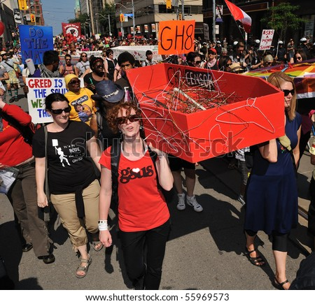 TORONTO-JUNE 25: Protesters walk with model of red coffin at G20 Protest on June 25, 2010 in Toronto, Canada. - stock photo