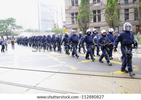 TORONTO-JUNE 26:  Riot police group marching on the streets  after a police car was torched nearby during the G20 Protest on June 26, 2010 in Toronto, Canada.