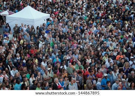 TORONTO - JUNE 21: Thousands of enthusiastic fans enjoy the free Toronto jazz festival concert at Nathan Phillips Square in Toronto on June 21, 2013. - stock photo