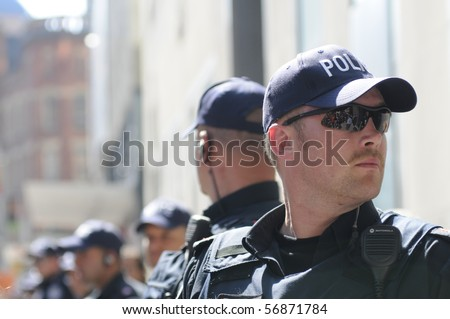 TORONTO-JUNE 25:  Toronto Police officers keeping a close eye on the rally during the G20 Protest on June 25, 2010 in Toronto, Canada. - stock photo