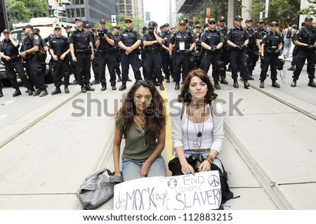 TORONTO-JUNE 27:   Two unidentified teens  doing a protest by sitting on the streets in front of the barricade of the police officers during the G20 Protest on June 27, 2010 in Toronto, Canada. - stock photo