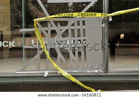 """TORONTO-JUNE 27: """"Urban Brick"""" broken store front window by violent protesters at G20 protest on June 27, 2010 in Toronto. - stock photo"""