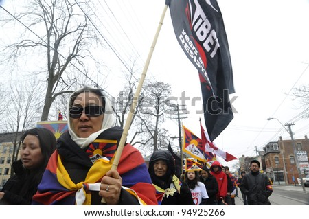 TORONTO - MARCH 10: An unidentified woman holding a Tibetan Resistance  flag marching in a rally organized to protest against the Chinese occupation of Tibet on March 10 2009 in Toronto, Canada.