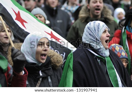 TORONTO-MARCH 16: Group of Syrians chanting slogans during a protest rally organized to raise awareness and commemorate two years of Syrian revolution on March 16, 2013 in Toronto, Canada. - stock photo