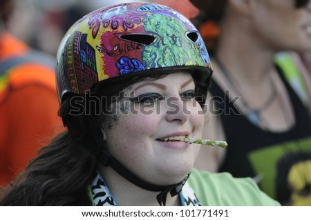 TORONTO - MAY 5:  A marijuana legalization activist with a marijuana cigarette during the    14th annual Global Marijuana March on May 5  2012 in Toronto, Canada. - stock photo