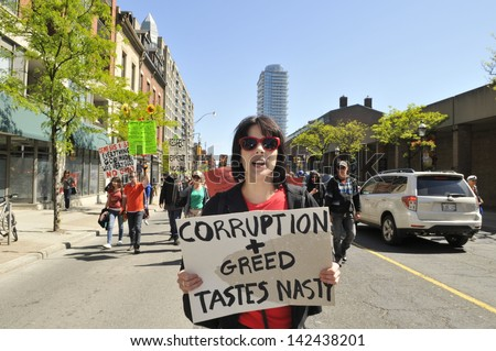 TORONTO-MAY 25: A teenage girl walking with a sign saying that GMO giant Monsanto is corrupt and greedy during a rally  against GMO giant Monsanto on May 25, 2013 in Toronto, Canada.