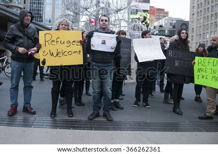 TORONTO - NOVEMBER 22: Men and women of all ages and religion standing together during a solidarity rally to welcome Syrian refugees to Canada  on November 22, 2015 in Toronto,Canada. - stock photo