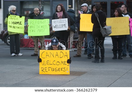 TORONTO - NOVEMBER 22: People with colorful posters gathered at Yonge & Dundas to  support the incoming Syrian refugees into Canada during a solidarity rally on November 22, 2015 in Toronto,Canada.