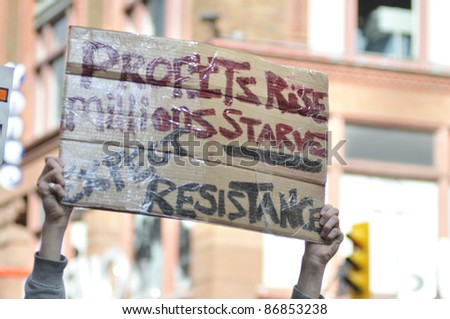 TORONTO - OCTOBER 17:  A  protestor holding a placard denouncing capitalism and justifying resistance during the Occupy Toronto Movement on October 17, 2011 in Toronto, Canada. - stock photo