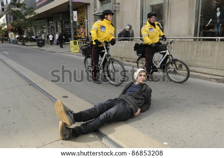 TORONTO - OCTOBER 17: A protestor laying on the street  while police keep a close eye on him  during the Occupy Toronto Movement on October 17, 2011 in Toronto, Canada. - stock photo