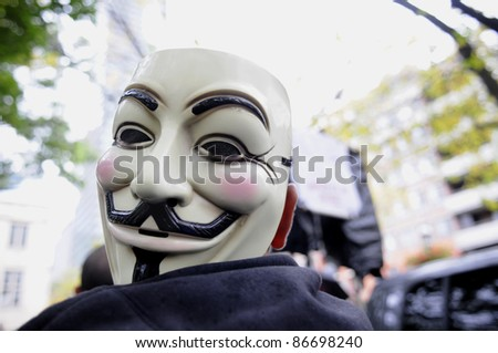 TORONTO - OCTOBER 15: A protestor listens to the speeches with his mask  tied to his shoulder during the Occupy Toronto Movement on October 15, 2011 in Toronto, Canada. - stock photo