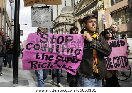 TORONTO - OCTOBER 17:  A  protestor walking with a sign with the  comment of warren buffet during the Occupy Toronto Movement on October 17, 2011 in Toronto, Canada. - stock photo