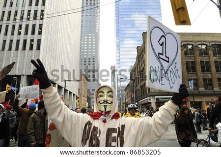 TORONTO - OCTOBER 17: A protestor wearing a guy fawkes mask walking in a rally  with placards during the Occupy Toronto Movement on October 17, 2011 in Toronto, Canada. - stock photo