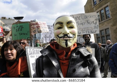 TORONTO - OCTOBER 17: A protestor wearing  guy fawkes mask walking in a rally  during the Occupy Toronto Movement on October 17, 2011 in Toronto, Canada. - stock photo