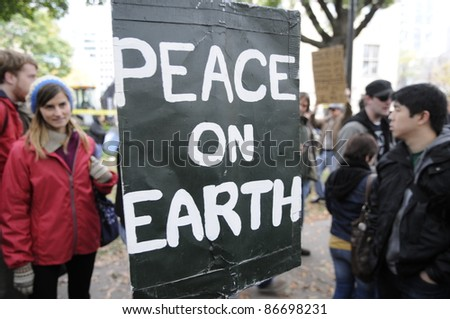 TORONTO - OCTOBER 15:  People stopping near a sign to have a closer look at the sign which urges for a peaceful world during the Occupy Toronto Movement on October 15, 2011 in Toronto, Canada. - stock photo