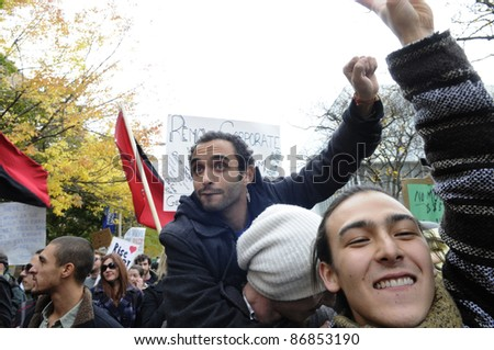 TORONTO - OCTOBER 17: Protestors  on each other shoulders during the Occupy Toronto Movement on October 17, 2011 in Toronto, Canada. - stock photo