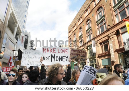 TORONTO - OCTOBER 17: Protestors walking  in a rally on yonge street during the Occupy Toronto Movement on October 17, 2011 in Toronto, Canada. - stock photo