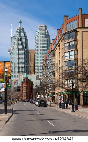 Toronto, Ontario - Apr. 24, 2016: Historic Toronto Flatiron building against the backdrop of modern skyscrapers, as seen from Front Street - stock photo