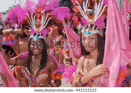 TORONTO, ONTARIO, CANADA - AUGUST 4, 2012: female participants, smiling, dressed in costumes, performing during annual Caribana Parade - North America's largest Caribbean Parade.