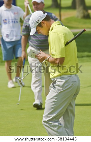 TORONTO, ONTARIO - JULY 21 : English golfer Paul Casey checks his notes during a pro-am event at the RBC Canadian Open golf on  July 21, 2010 in Toronto, Ontario - stock photo