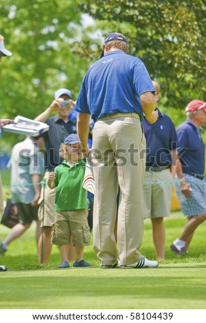 TORONTO, ONTARIO - JULY 21 : South African golfer Retief Goosen gives autograph to a little boy during a pro-am event at the RBC Canadian Open golf on  July 21, 2010 in Toronto, Ontario - stock photo
