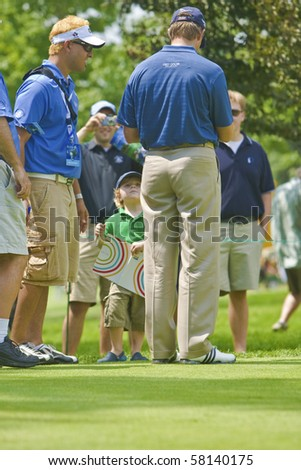 TORONTO, ONTARIO - JULY 21 : South African golfer Retief Goosen signs autograph for a little boy during a pro-am event at the RBC Canadian Open golf on July 21, 2010 in Toronto. - stock photo