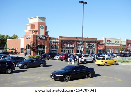 TORONTO - SEPTEMBER 14: A strip mall on September 14, 2013 in Toronto. In the U.S. and Canada, strip malls usually range in size from 5,000 square feet (460 m2) to over 100,000 square feet (9,300 m2). - stock photo