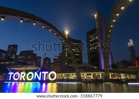 TORONTO - SEPTEMBER 6: Night long exposure of the fountain in Nathan Phillips Square with the illuminated City Hall and the Freedom Arches in the background, on September 6, 2015. - stock photo