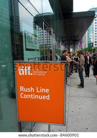 TORONTO - SEPTEMBER 13: People gather for rush line at the TIFF Bell Lightbox hours before film screening for the 36th Toronto International Film Festival Sept 13, 2011 in Toronto, Canada - stock photo