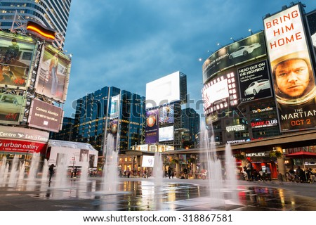 TORONTO - SEPTEMBER 12: People shop and relax at Yonge and Dundas Square in Toronto at dusk, illuminated by the lights of the colorful neon billboards and advertisement, on September 12, 2015. - stock photo