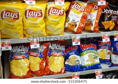 TORONTO - SEPTEMBER 14: Potato chips selection in a supermarket on September 14, 2013 in Toronto. The global potato chip market generated total revenues of US$16.4 billion in 2005. - stock photo