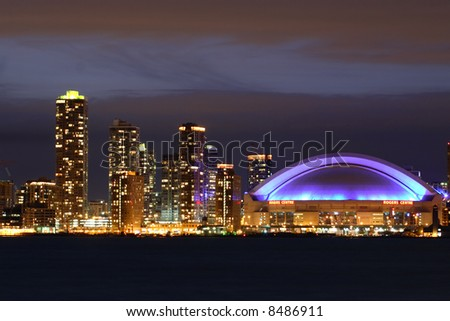 Toronto skyline and Rogers Centre (SkyDome) at night.