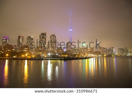 Toronto Skyline at night with a reflection in Lake Ontario - stock photo