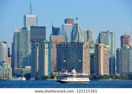 Toronto skyline in the day over lake with urban architecture and boat. - stock photo