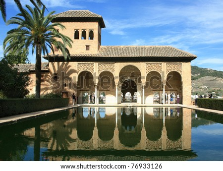 Torre de las Damas and its reflection in a pool in the Alhambra of Granada, Spain.