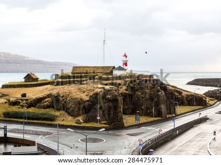 Torshavn, Faroe Islands, 7th February 2015. The old traditional lighthouse is surrounded by modern infrastructure - stock photo