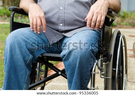 Torso and leg view of paraplegic man as he sits outside in his wheelchair. - stock photo