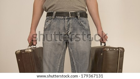 torso and legs of young man in a blue denim  jeans and gray shirt holding two retro old vintage suitcase in his hands  isolated on white background Copy space for inscription - stock photo
